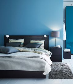 A modern blue and black bedroom with MALM bed in black and PAX wardrobe in high-gloss turquoise