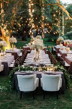 Long farm tables with neutral linens, bunches of baby's breath in tall cylinder vases and lush garlands. Strands of bistro lights and hanging fairy lights brought an air of whimsy to the space.