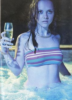"""Christina Ricci tests the waters, champagne in hand, in """"Poor Little Ricci Girl."""" Photographed by Carter Smith. Styled by Joe Zee"""