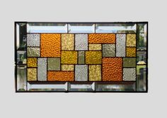 This stained glass panel is sampling of shades and textures of glass in a geometric abstract pattern in amber and clear. The panel is approximately 19 1/4 x 101/4.  The panel is then finished off with 12 beveled pieces for the outside beveled border  The panel can be hung in either vertical or horizontal direction. The patina on the solder is black and the zinc frame is left in the silver tone. To see more abstract geometric panels http://www.etsy.com/shop/sghov...