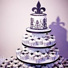 White and Black. By:  Celebrating Life Cakes, St. Louis, MO. The couple designed the black-and-white display with their baker. They found the stand online and finished the look with a fleur de lis topper and filigree liners.