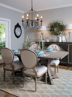 The dining room is illuminated with a dark metal chandelier and staged with bright, comfortable chairs and a dining table set with blue plates and French Country accessories and greenery.  The new French doors open to the backyard and offer additional natural light.  A magnolia wreath hangs above a sideboard displaying two lamps and and white serving dishes.