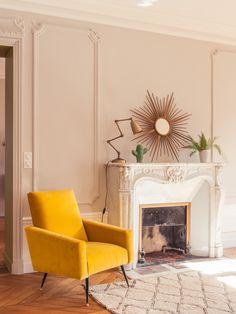 Appartement décoré par Marion Alberge sur Paris | épingle par l'agence Skéa | cheminée ancienne avec fauteuil vintage tapis berbère miroir soleil or et lampe à poser dorée | esprit vintage et chic parisien