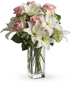 Teleflora's All Around Heavenly and Harmony Bouquet. Stunning in its simplicity, this innocent harmony of light pink roses and snow white lilies are a heartfelt way to send your very best. The classic, clear rectangular glass vase keeps the focus on the heavenly beauty of the blooms.