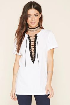 A boxy knit top featuring a lace-up neckline, longline silhouette, and short sleeves with stitched cuffs. #summerdaze