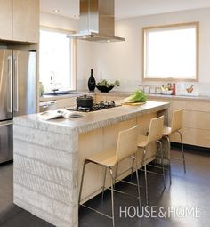 The island, with a waterfall-style concrete counter, steals the scene.