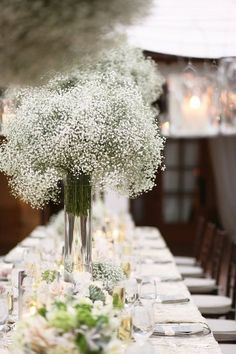 baby's breath center piece. Love the tall clear vases so guests can stiil see each other across the table.