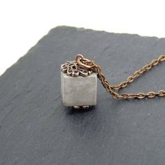 🎅🎅🎅 This enchanting piece of jewelry consists of a light grey cube, cast from concrete, with finishes in antique copper. A small, slightly oriental-looking, eye-catcher. A piece of jewelry to fall in love with! The cube looks halsnah worn as stylish as on a slightly longer chain.