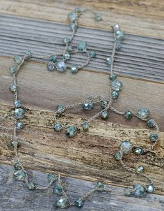 Opalescent aqua / teal crystal glass beads are hand knotted in a modern, graduated pattern to create this very versatile piece. Can be worn many ways. Single, doubled, lariat style, and also wrapped a
