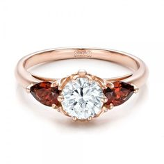 #101156 This elegant engagement ring features a round brilliant cut diamond set in rose gold, with garnet and custom filigree accents. It was created for a...