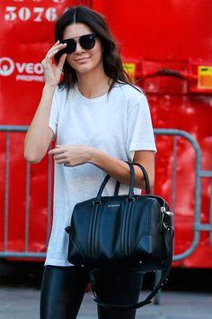 Street style da modelo Kendall Jenner com legging preta, t-shirt branca e bolsa preta.