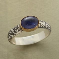 SWEET PEA RING An iolite, nestled in a 14kt gold bezel, blooms on a hand-carved sterling silver band