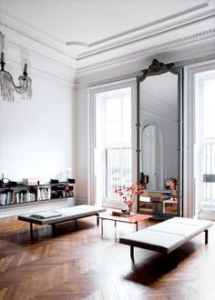 Gorgeous floor to ceiling windows, crown moulding and herringbone floors. paired with Venetian mirrors, French crystal chandeliers and mid-century benches and coffee table.