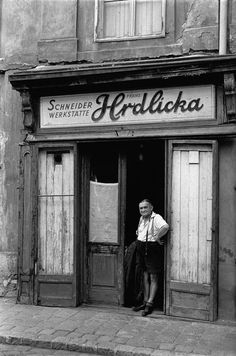 by Erich Lessing AUSTRIA. Life in post-war Vienna: A tailor in traditional leather shorts stands in front of his shop. Shop windows are still boarded up after war damage. Heart Of Europe, Good Old Times, Photographer Portfolio, Vienna Austria, Second World, Magnum Photos, Photo Black, Black And White Pictures, Facades