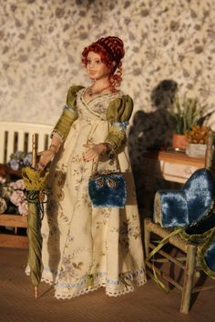 """Marie, minis2you - """"Lydia"""", OOAK porcelian figure in Regency dress. She is wearing a hand-sewn day dress in cotton and a removable cape in finest silk velvet and an little handbag and a hat and umbrella. Under her dress she wears lace trimmed pantaloons.  selling on etsy for $248.49"""