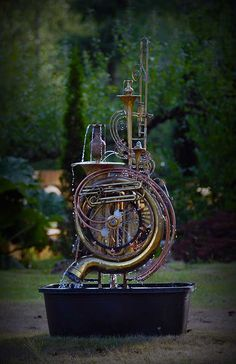 TubaTango – 73 in H, 46 in W, 26 in. D. Musical instrument fountain sculpture – Copper tube, Upcycled musical instruments, tubas, trumpets, a trombone, bicycle wheel, brass and glass pieces.