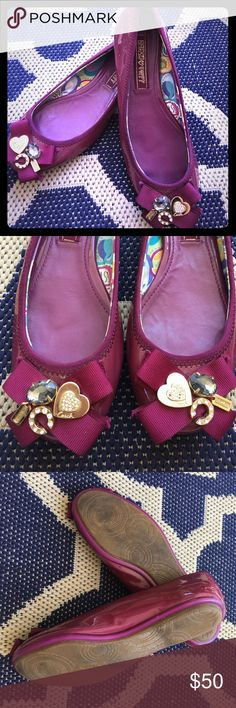 Coach Poppy flats Size 6.5 flats, color is purple magenta patent leather. Gently  used condition. No holes, cracks or tears. A few missing rhinestones in the heart charm. Minor scratches on the charms but all intact on a grosgrain bow. Minor scuffs. Minor inside wear. Minor wear to the rubber sole. Questions/reasonable offers welcome. Enjoy! Coach Shoes Flats & Loafers