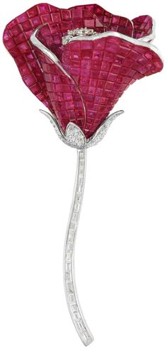 White Gold, Invisibly-Set Ruby and Diamond 'En Tremblant' Flower Brooch, Alexis.  18 kt., the petals invisibly-set with numerous square-cut rubies approximately 45.00 cts., centering 7 round 'en tremblant' diamonds, supported by pave-set diamond leaves, the stem set with 20 baguette diamonds, altogether approximately 1.96 cts., signed Alexis, no. 02, approximately 16 dwt. Via Doyle New York.