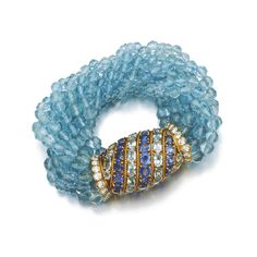 AQUAMARINE, SAPPHIRE AND DIAMOND BRACELET, CARTIER, 1960S Of torsade design, the barrel clasp set with oval sapphires and aquamarines and accented with brilliant-cut diamonds, suspending ten lines of facetted aquamarine beads, length approximately 200mm, signed Cartier, numbered, French import marks.