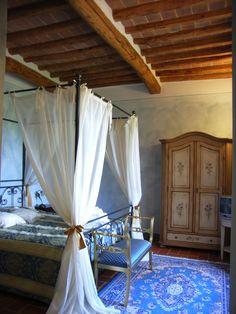 La bellissima Suite Fiordalisi dell'agriturismo romantico Taverna di Bibbiano, con splendido letto a baldacchino e raffinati mobili artigianali. Vista sul parco dell'agriturismo e sulla campagna.