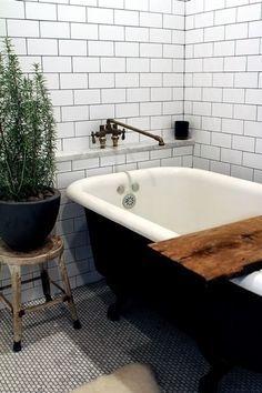 Farmhouse feel...subway tiles, dark grout, black tub, rustic fixture, rosemary