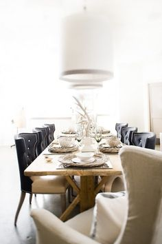 details I like: wooden dining table, wingback chairs (for all! how lovely), low-hanging lamps, woven dinner plates • photo uncredited