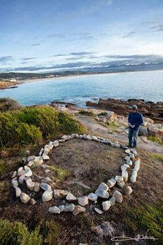 FACEBOOK 22 Aug. Imagician (photo). 'The Tales of Waves' by Won-Gil Jeon, on Lookout Beach in Plettenberg Bay. Made of stones he broke with a hammer, he placed the stones in a circle to symbolise connectivity and encourage people to look at nature with different eyes. Site_Specific #LandArtBiennale. #LandArt #Plett