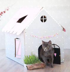 De papelão, esta casinha leva cores claras e estilo feminino, com direito a um vaso na entrada.