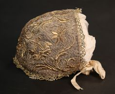 Infant's bonnet, 1730s. The linen ground entirely worked in silver threads with raisedwork gold thread lilies, edged in gold bobbin lace.