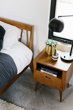 Mid Century Modern Bedroom Design with Wool Cream Rug, Parachute Quilt Bedding and Walnut Bedframe and Nightstands. Black Lamps, Roman Shades and Custom Beaded Art above Headboard