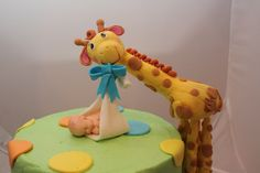 Special Delivery! - This is the cross between a customer requesting a giraffe baby shower cake, and me really really wanting to use my new baby mold! The customer loved it and so did I! Iced in buttercream with MMF dots and stripes. The rest of the decorations are gumpaste. Matching cupcakes with MMF dots.