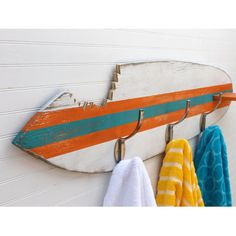Complete a coastal look in the powder room or hang towels beside the pool with this surfboard-shaped wall rack, showcasing a playful sharkbite cutout and war...