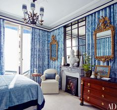 Timothy Corrigna's Paris bedroom is a vision in blue, with the mirrors hung directly onto the curtains. | archdigest.com