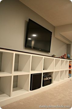 TV mounted on wall with cube shelves underneath - basement movie room to store pillows and blankets