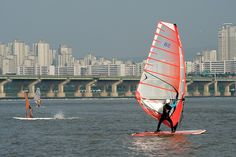 A wind surfer glides smoothly across the waters of the the Han River.  Other popular water activities such as water skiing, wakeboarding, fly fishing, and yachting are available at the Ttukseom, Jamwon, Ichon, and Mangwon areas of Seoul. For more info on aquatic sports, visit: http://english.seoul.go.kr/lh/leisure/mla.php?pidx=7