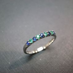 Blue Sapphire and Emerald in 14K white gold. color of my wedding ring and coops birthstone together, which would make a great stacking ring