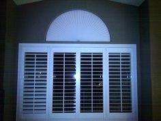 Cost effective way to cover an arched window: Cut cardboard or another opaque material to size and paint it white then cover with a Ready Arch paper shade. Blocks light, insulates and costs a fraction of custom shutters or blinds.