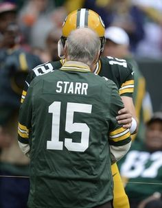 Green Bay Packers quarterback Aaron Rodgers (12) greets Green Bay Packers great Bart Starr while running onto the field before the game agai...