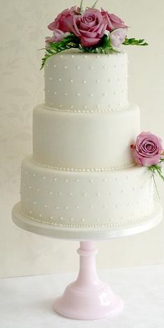 Pearl studded cream wedding cake with deep pink roses on a light oink cake stand. Sweet and simple for the classic bride.