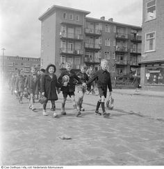 1944 - 1945. Children walk to a soup kitchen in Amsterdam during the hongerwinter. During the Winter of 1944-1945 Dutch rail workers went on strike to resist the German occupation. The Germans punished the population by putting a hold on all maritime transport. This cut off all food and fuel delivery to Amsterdam. Photo Nederlands Fotomuseum / Cas Oorthuys. #amsterdam #worldwar2 #Hongerwinter