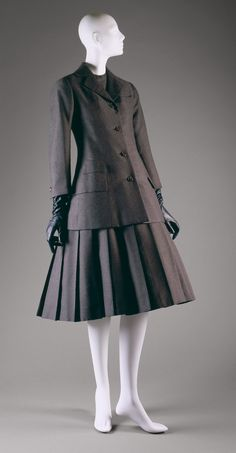 Ensemble  Design House: House of Dior (French, founded 1947) Designer: Christian Dior (French, Granville 1905–1957 Montecatini) Date: spring/summer 1955 Culture: French  A signature Dior 1950's dress with full skirt and button up jacket. It was transformed from a men's suit with men's tailoring techniques and fabrics.