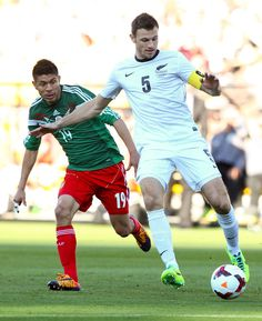 Tommy Smith of New Zealand passes under pressure from Oribe Peralta of Mexico during leg 2 of the FIFA World Cup Qualifier match between the New Zealand All Whites and Mexico at Westpac Stadium on November 20, 2013 in Wellington, New Zealand.