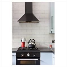 wall hood with tile | GAP Interiors - Black cooker and extractor hood with white tiled wall ...