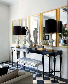 Love the effect of the five gold trimmed mirrors with the long, thin console in black and gold.