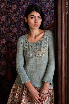 pale blue scoop neck sweater with lace above empire line, 3/4 sleeve, on model in front of floral background