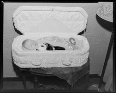 Post mortem image of baby with toys in casket, 1950-1953.