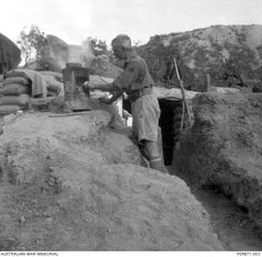 WWI, 1915, Gallipoli; A soldier cooks on an improvised stove, made from a drum, outside his dugout. The soldier is either Billy West (identity unknown) or Private (Pte) Thomas Sydney (or Sidney) Harrison (see P09871.003)