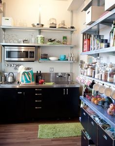 hang cups or pans from the bottom. Spices in mason jars in the middle/cookbooks and tin cans up top?