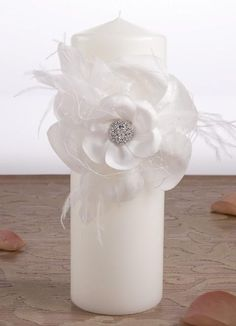 Somerset Wedding Unity Candle made of solid wax available in white or ivory.  The center of the candle is decorated with a matching satin band. The front of the band is decorated with a flower adornment that is made of layered satin petals, french netting, and feathers. The center of the flower is decorated with an Austrian crystal embellishment.