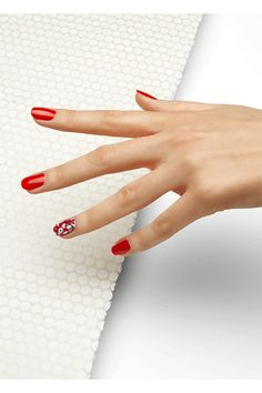 """Start by painting each nail with a fiery red hue, like Essie Gel Nail Color in Meet Me At Sunset, seen here. Then loosely dab pastel blue, fuchsia, and plum polishes on your ring finger until all the colors meld together. Finish with a few black dots """"to create the look of flowers in the mix of colors,"""" she suggests."""